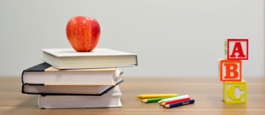 Apple perched atop school books.