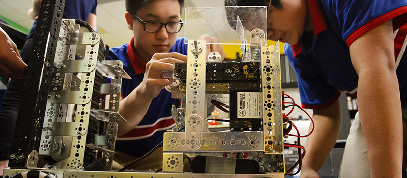 Teenage STEM students assemble a project