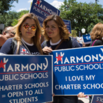 Two female Charter School supporters hold signs supporting their cause