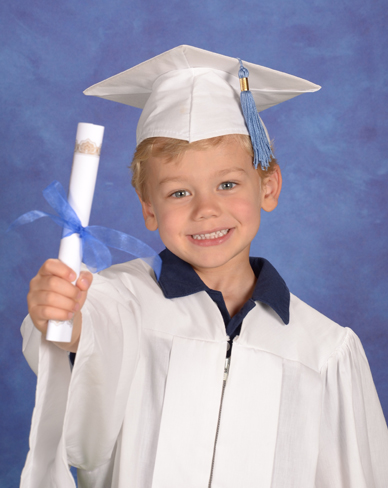 An image of a young boy dressed in cap and gown holding a diploma