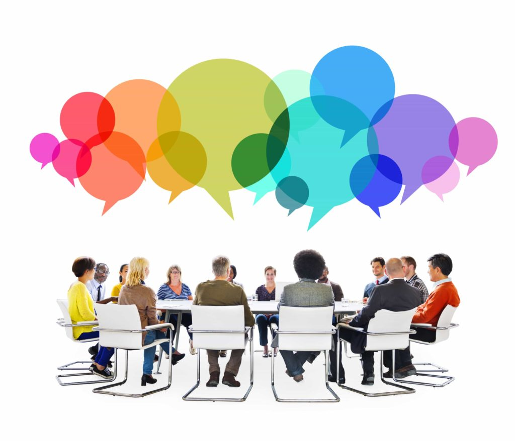 An image of people sitting around a table having a meeting with colored thought or speech bubbles.