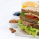 Image of a sandwich, fruit and nuts depicting a lunch meal